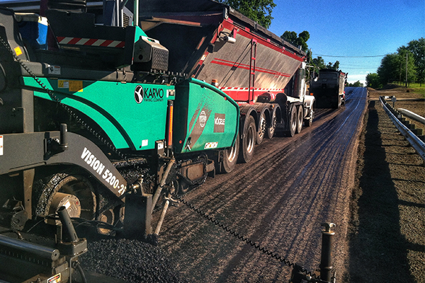 Asphalt being laid on a road by Karvo Paving Company's Asphalt Division